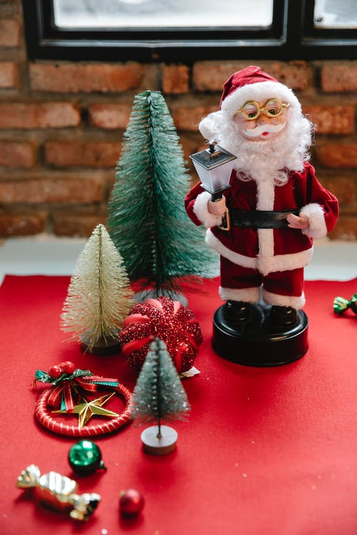 Saint Nicholas statuette with lantern near assorted New Year decoration on red fabric in house