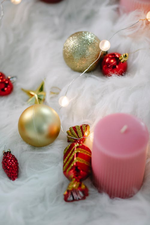 From above of sparkling golden baubles composed with Christmas decorations and candle on fluffy soft blanket