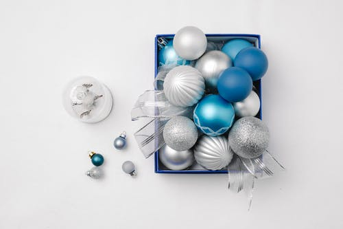 Top view of decorative different New Year baubles in box prepared for celebrating festive holiday on white background