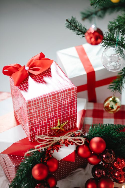 Colorful red boxes of presents decorated with Christmas baubles