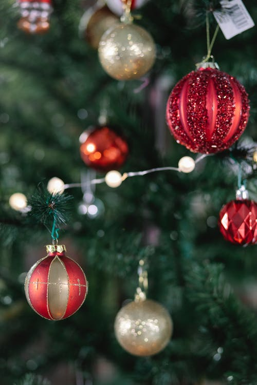 Green branches of coniferous tree decorated with red and golden Christmas balls with glowing garland on blurred background during holiday