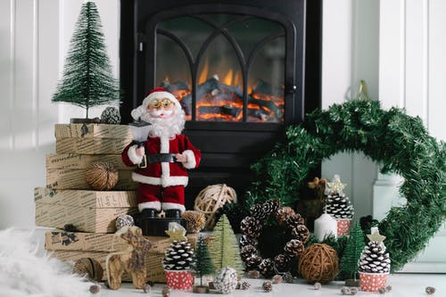 Statuette of Santa Claus placed on wrapped gift boxes near Christmas decorations at warm fireplace with green wreath at home