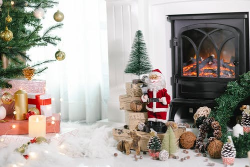 Cozy light room with gift boxes under Christmas tree and Santa Claus near holiday decorations placed on white cozy fabric at home with fireplace and burning candles