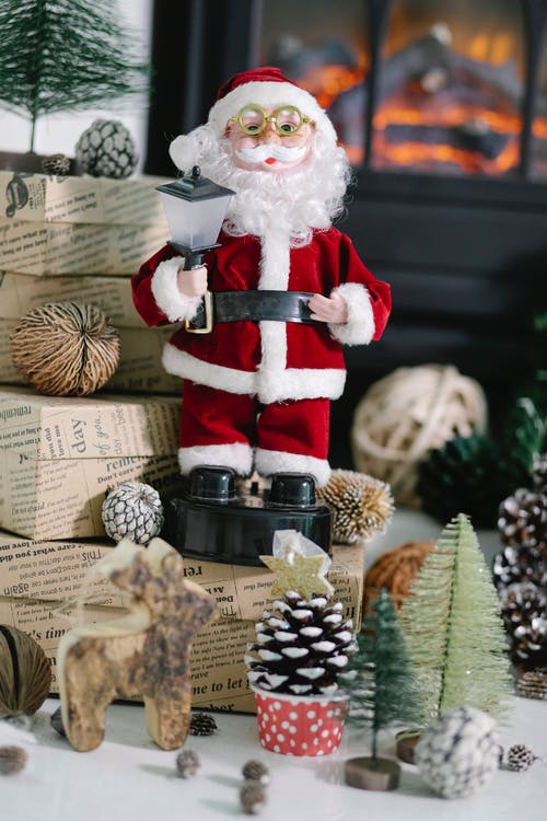 Santa Claus toy placed on present box near Christmas decorations in cozy room with fireplace on blurred background during holiday