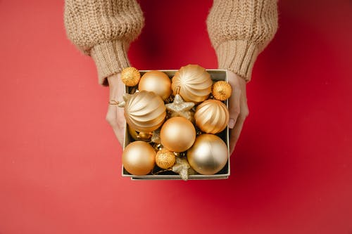 Crop woman with Christmas baubles in box