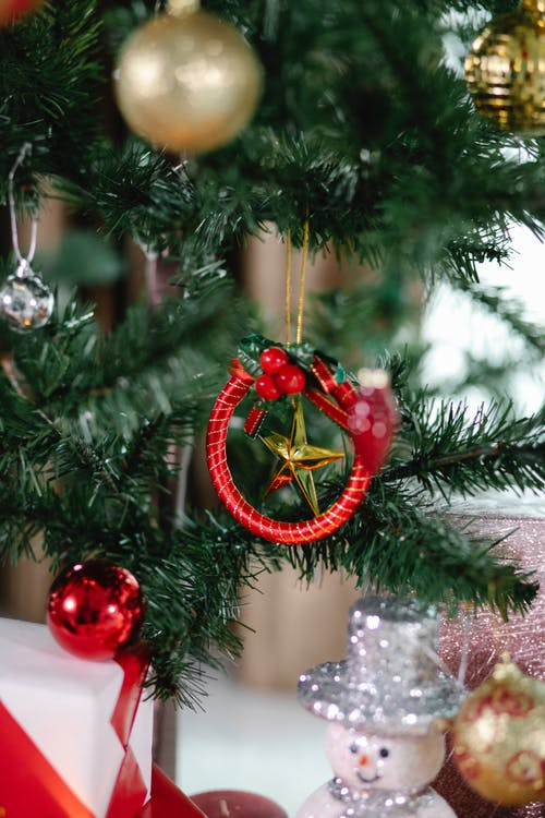 Branches of coniferous tree decorated with baubles star and red Christmas toy in light room with snowman on blurred background