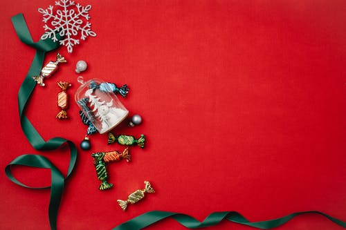 Christmas decorations with ribbon on red surface