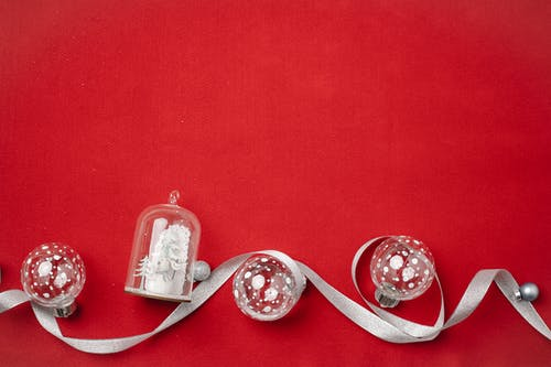Top view of Christmas composition with small Christmas tree baubles and souvenir covered with glass dome and wavy silver ribbon on red background