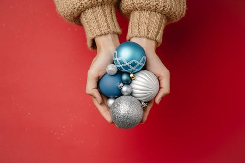 Top view of unrecognizable female in warm knitted clothes holding Christmas tree hanging baubles on red background