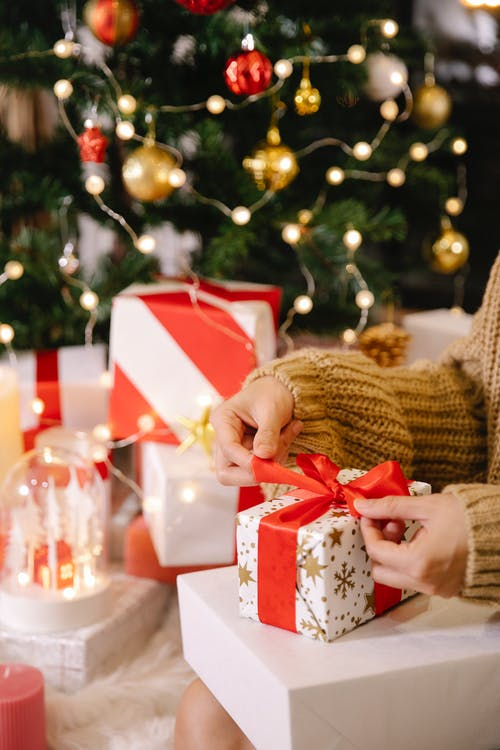 Woman preparing Christmas present near decorated fir tree