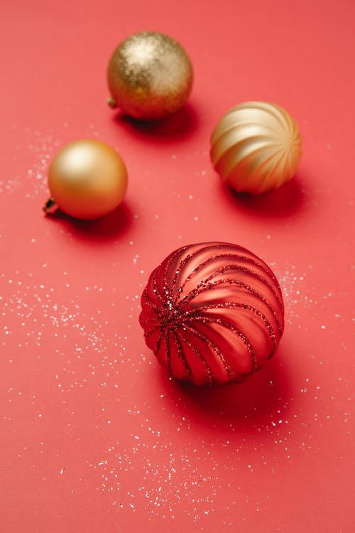 From above of Christmas red and golden baubles sprinkled with shiny glitters on red background