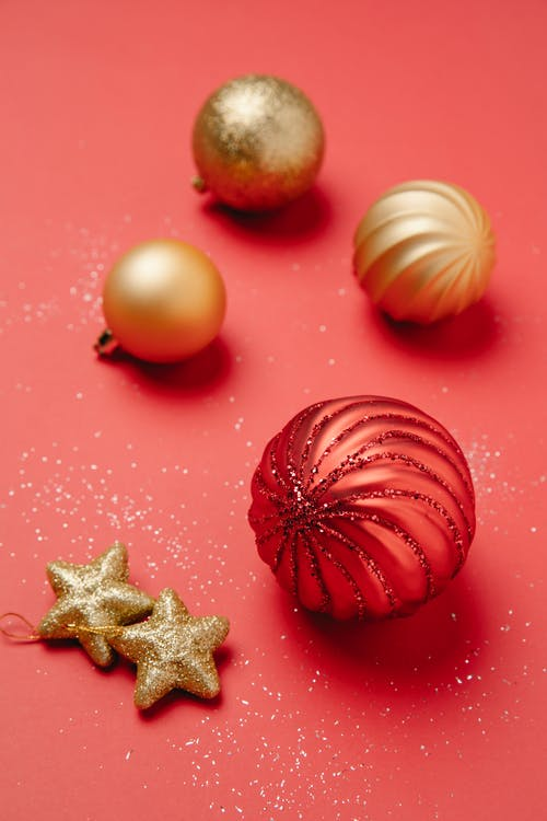 From above Christmas composition of hanging shiny baubles and stars on red background