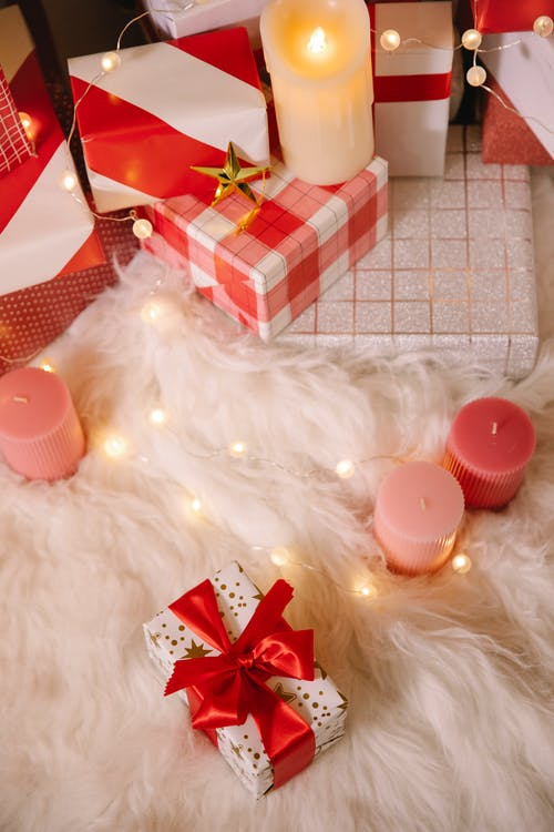 High angle of Christmas composition with wrapped boxes with presents candles and lighted garland on  white fur