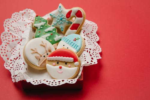 High angle of small box with Christmas biscuits decorated with colourful icing on white doily