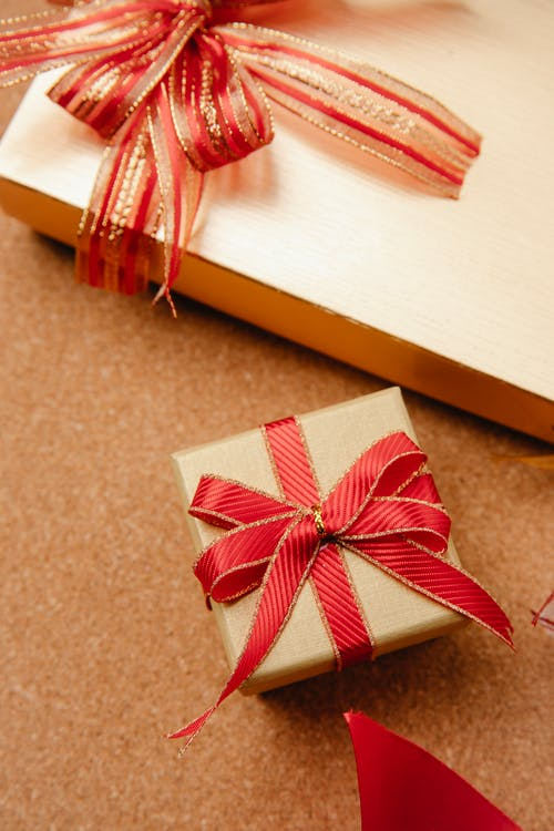 From above wrapped Christmas gift boxes decorated with red ribbons on wooden table