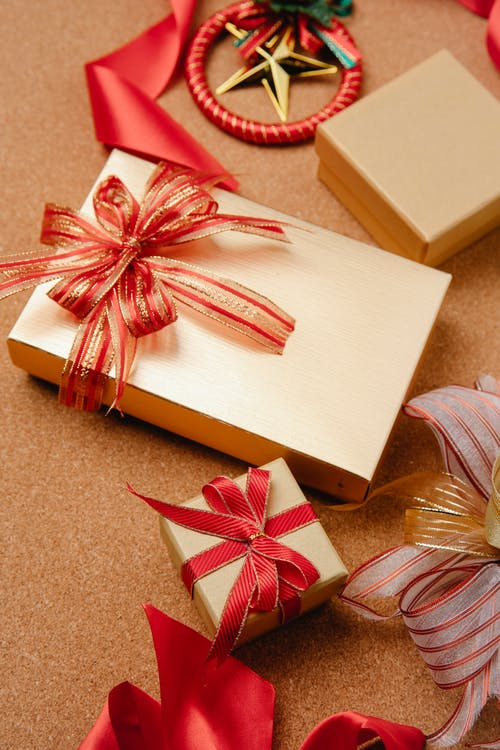 High angle of traditional Christmas gift boxes wrapped in golden paper and decorated with red ribbons