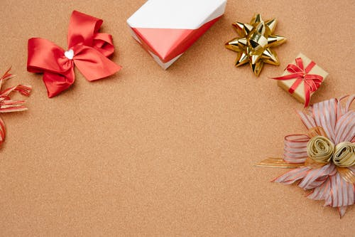Gift boxes and decorative bows on cork surface