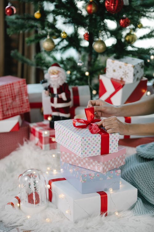 Crop anonymous female sitting near Christmas tree and tying red ribbon in bow on present box