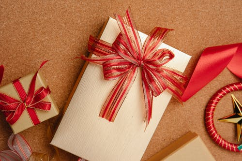 From above of big and small boxes wrapped in golden paper and decorated with red ribbons on table
