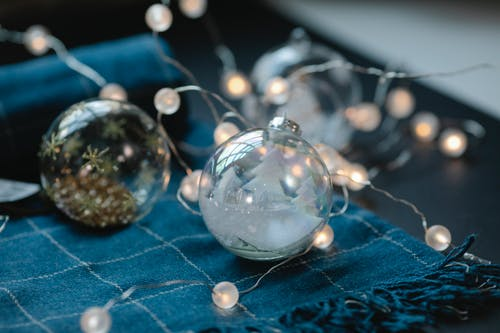 Transparent Christmas baubles filled with ornaments on table with blue warm scarf and glowing garland