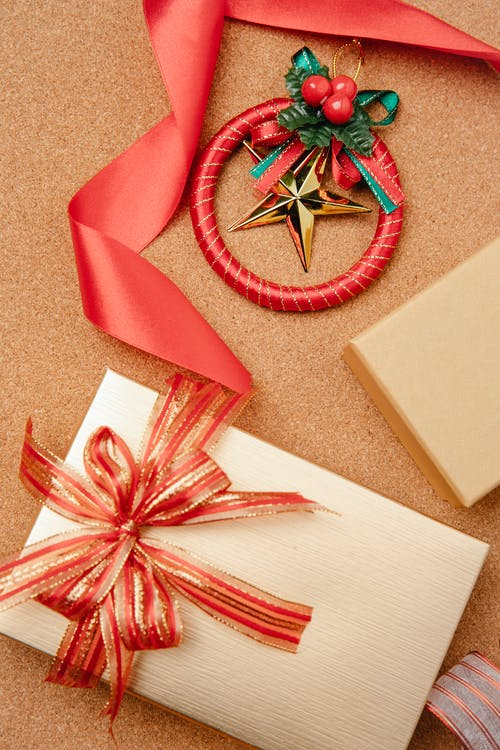 From above of Christmas gift box wrapped in golden paper and decorated with red ribbon and festive baubles on table