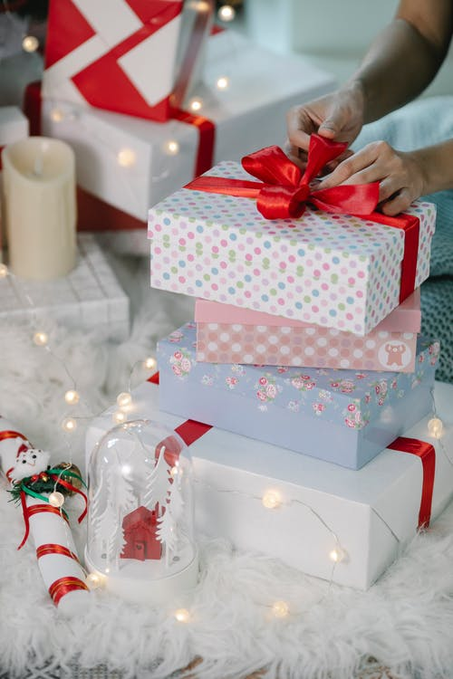 Woman preparing for Christmas and decorating gift box