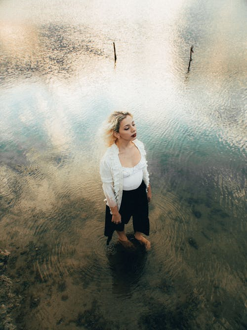 From above full length young attractive female in casual clothes standing in shallow lake water in peaceful park in daylight