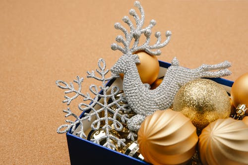 High angle of blue box with Christmas festive golden baubles shiny reindeer and snowflake