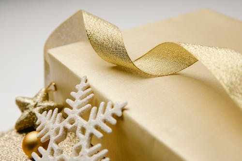 Closeup of golden wavy ribbon on wrapped box with Christmas present and festive baubles