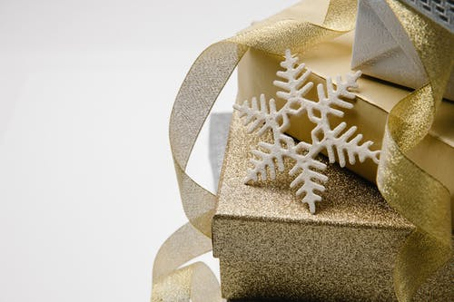 Christmas gift boxes in golden paper and shiny ribbon