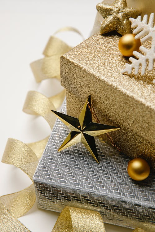 Christmas composition of gift boxes wrapped in silver and golden paper with shiny baubles and twisted ribbon