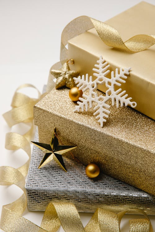 Christmas composition of stack of gift boxes wrapped in silver and golden paper cute baubles and wavy ribbon
