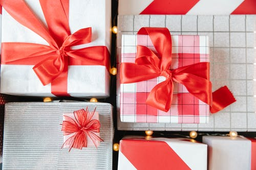 Gift boxes with red ribbons and lighted garland
