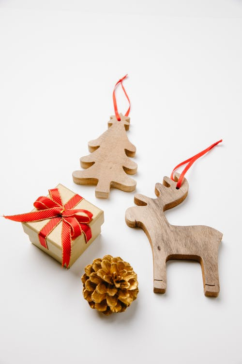 Top view of wooden toys in shape of reindeer and Christmas tree near small gift box and bump placed on white surface