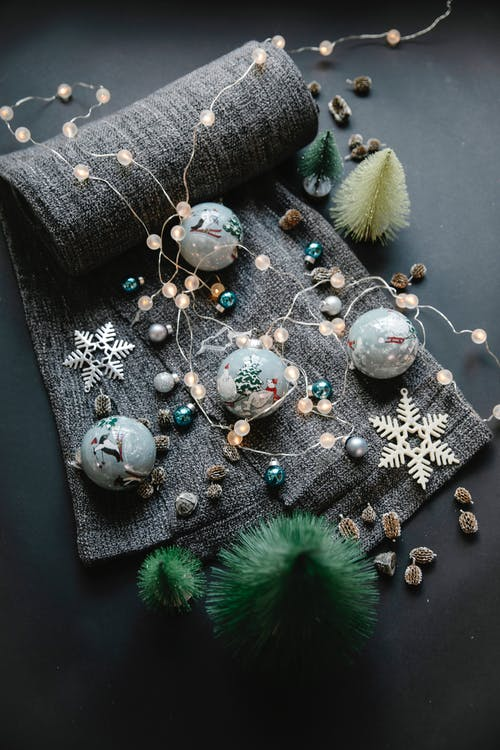 High angle of Christmas painted balls on textile near various decorations with small fake spruces and wreath on black surface