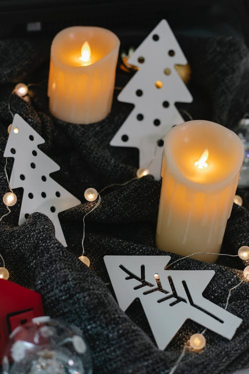 From above of composition of decorative candles and toys in form of fir trees placed on gray fabric