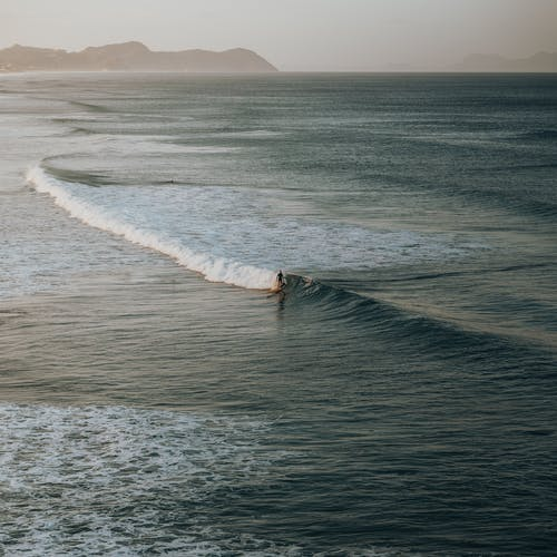 Person Surfing on Sea Waves