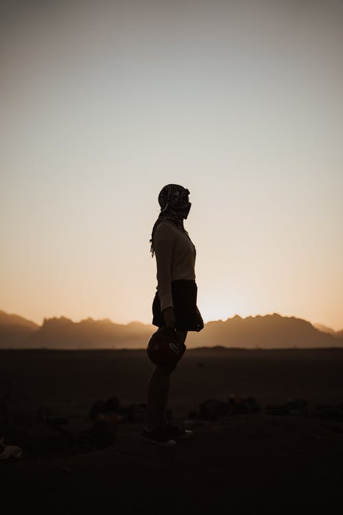 在日落时站在岩石上的人的身影