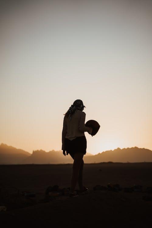 日落期间站在棕色沙滩上的白衬衫和黑色裤子的男人