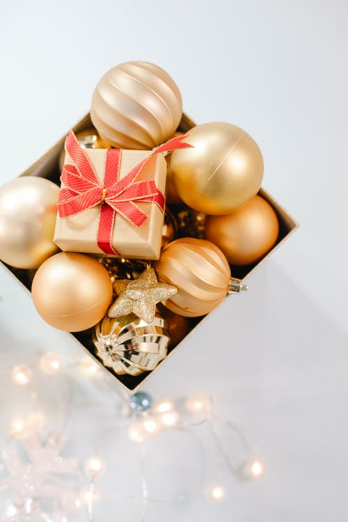 Box with golden baubles placed on white surface