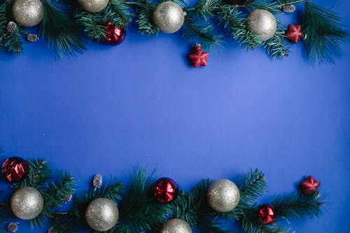 Branches of fir with Christmas baubles against blue background