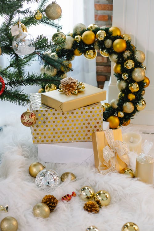 Golden gift boxes placed on carpet near Christmas tree with baubles placed in decorated light room in apartment