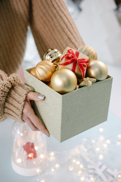 Female in sweater holding box with golden Christmas baubles