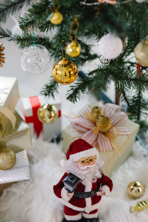 Santa Claus Figurine Beside Gold Baubles