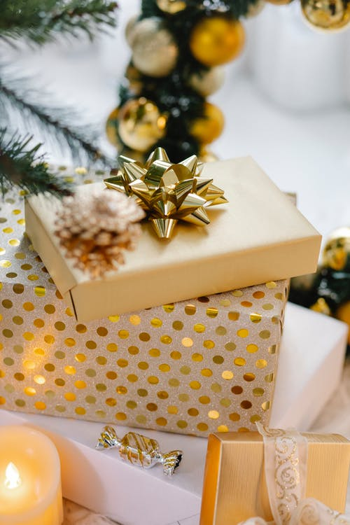 Christmas decorations with pine cone over golden presents and glowing candle at home
