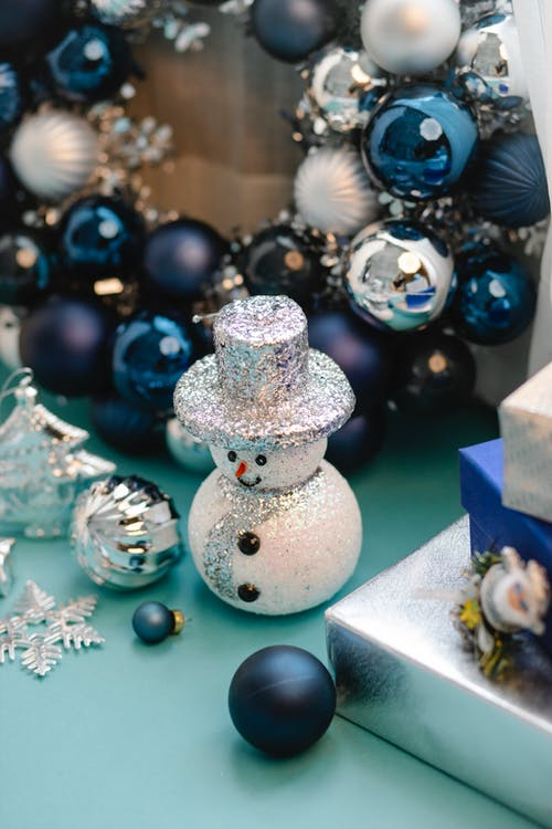 High angle of shiny snowman near Christmas wreath and decorations for festive party at home