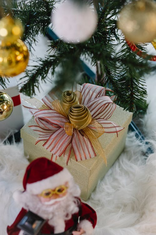 Gift box and Santa Claus toy under Christmas tree