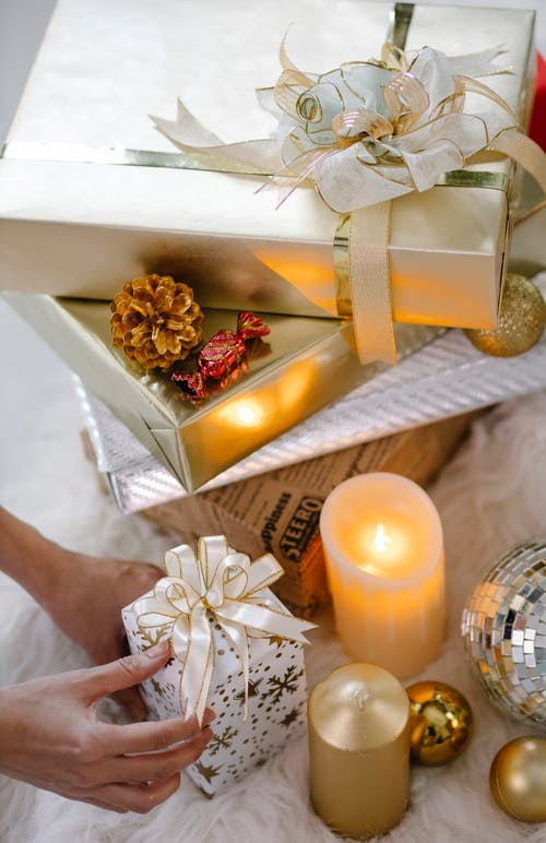 Crop person with Christmas gift box and decorations
