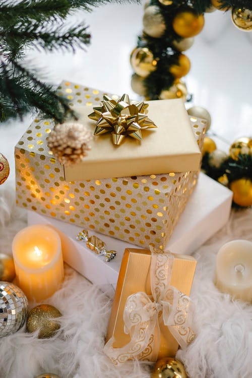 Colorful gift boxes and candle under Christmas tree