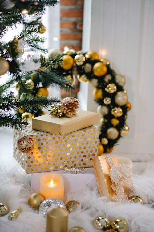 綠色聖誕樹旁邊的棕色和白色禮品盒